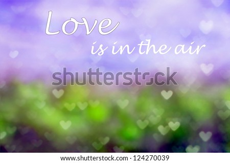 Fantasy background with a bokeh of hearts and words in the sky saying ; Love is in the air