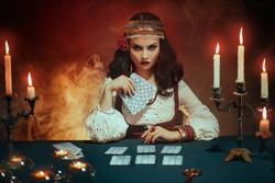 Fantasy beautiful girl in image of gypsy witch sits at table in dark gothic room. Art Red costume. Fortune teller magical woman reading future on tarot cards. Ritual candles burning, seance, smoke.
