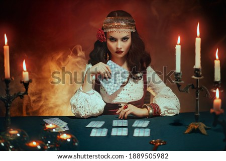 Fantasy beautiful girl in image of gypsy witch sits at table in dark gothic room. Art Red costume. Fortune teller magical woman reading future on tarot cards. Ritual candles burning, seance, smoke. Stock foto ©