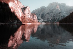 Fantasy colors of the Dolomite mountains in the Braies lake towards sunset with boats moored, South Tyrol, Italy. Concept: relaxation in nature, famous natural places, fantasy colorful scene