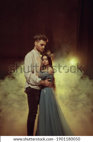 Fantasy couple hugging in dark room full white smoke. Image of lovers - king and queen. Medieval male prince in golden crown, vintage costume clothing. Girl Princess in long glamorous blue dress gown