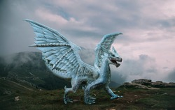 Fantasy dragon stands on the top of the mountain. A huge dangerous animal with large, sharp wings. Beautiful alpine nature background, dramatic gray blue sky with white clouds.