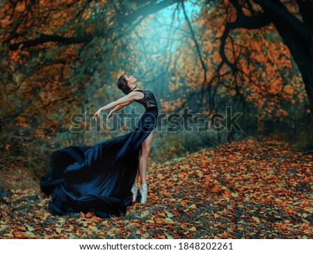 Fantasy fairy beautiful woman in a medieval black silk dress dancing. Princess girl in misty autumn forest. Art processing yellow trees bright divine magic light. Fashion model ballerina dancer posing