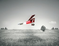 Fantasy flight of an old red airplane flying on a field and sky in black and white