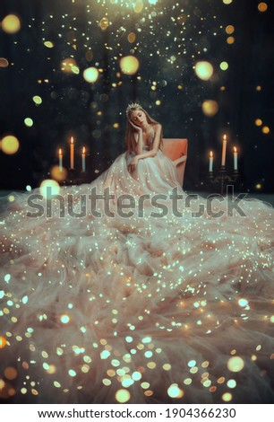 Fantasy girl princess star sits on armchair in luxurious pink glamorous shining dress, long skirt silk train. Woman queen asterisk, glows with golden lights, white light bulbs garlands christmas magic