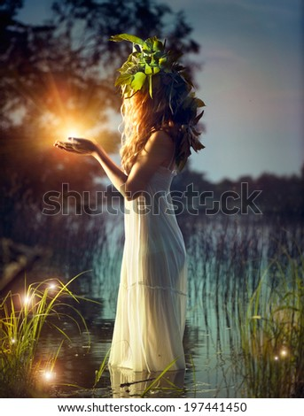 Stock Photo Fantasy girl taking magic light in her hands. Mysterious Night scene. Witch standing in the river and practice witchcraft. Fairytale