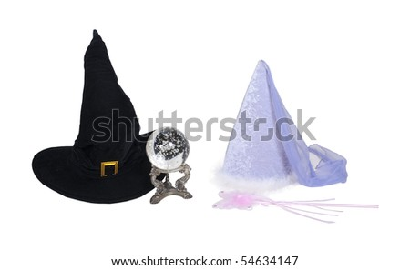 Fantasy good and evil shown by a traditional large pointed black witch hat with crystal ball with a princess hat with fairy wand - path included