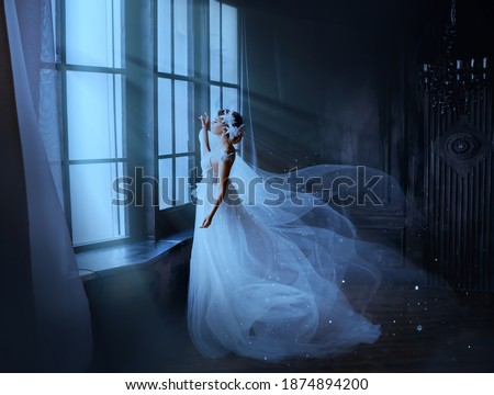 Fantasy gothic woman ghost bride stands by window in black dark room, magic moon light. Fairy snow queen in white dress, cape flying in wind, train skirt fluttering motion. Medieval vintage princess.