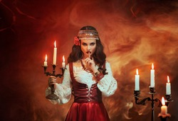 Fantasy Gypsy woman in red vintage dress. Girl witch fortune teller holds candlestick burning candles. Room in magical fire. Spiritual Art photo. finger touches lips gesture of secret mystery silence