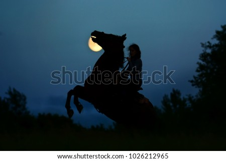 Fantasy horror moonlight with silhouette of the dark horse rearing up. Wild stallion with rider under full moon in night. Magic horror and halloween atmosphere background. Сток-фото ©