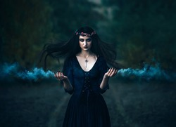 Fantasy horror woman witch medieval old purple outfit clothes dress. key on neck. Gothic magic portrait. Evil  makeup face Art scary Magician spell smoke hands. Hair flutter fly wind night forest road