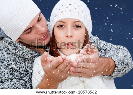 Fantasy image of young couple blowing snow