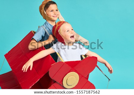 Fantasy, imagination of children. Two happy kids sit inside of cardboard red airplane imagine flight in sky. Big dream to be pilot