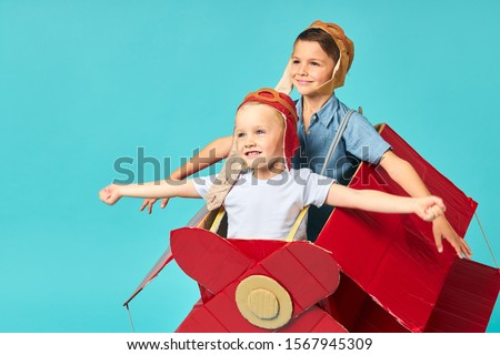 Fantasy, imagination of children. Two kids sit inside of cardboard red airplane imagine flight in sky. Big dream to be pilot
