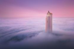 fantasy lighthouse over fog at sunset