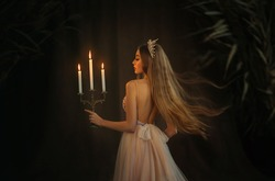 Fantasy medieval girl princess walks in dark gothic room. Woman queen is holding candlestick with burning candles in hand. Dress with open back, crown, long loose blonde hair flying in motion. Go away
