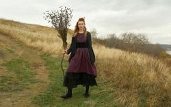 Fantasy. Medieval style. Fashion. Tall young model. Unusual historical clothes. Nature background. Red hair, freckles, beautiful face. Witch with broom. North. Celtic culture. Autumn. Yellow field