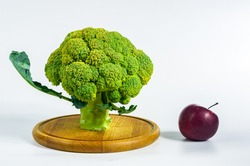 Fantasy mini landscape - tree made with broccoli and apple on a white background. The concept of the appearance of an idea, the symbol of Newton's apple