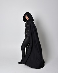 fantasy portrait of a woman with red hair wearing dark leather assassin costume with long black cloak. Full length standing pose  isolated against a studio background.