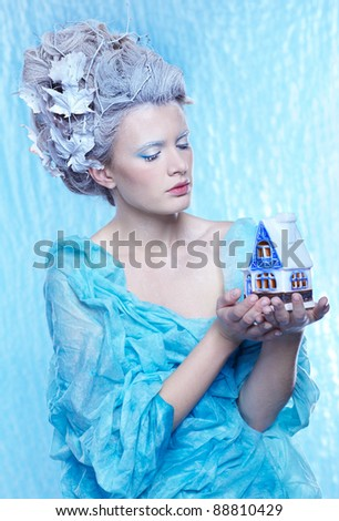 fantasy portrait of beautiful young woman imaging ice fairy on frozen blue with toy house