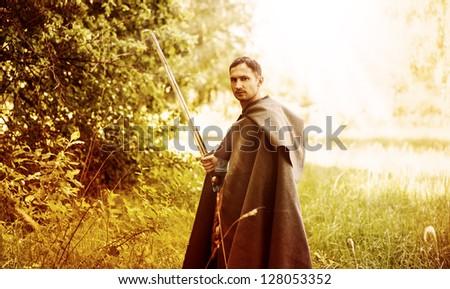 Fantasy portrait of handsome dangerous man with medieval sword