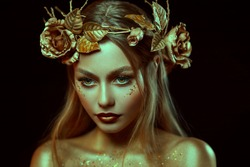 Fantasy portrait of woman with golden skin. Girl goddess in wreath, gold roses, accessories. Beautiful face, steel glitter makeup. Artistic photo, black background. Elf fairy princess. Fashion model