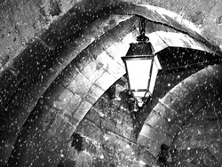 Fantasy scene,black & white,  one street lamp hanging from the top of the arch in cold winter night. Saint-Malo, France,