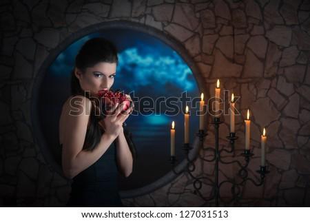 Fantasy style portrait of demonic woman biting a pomegranate