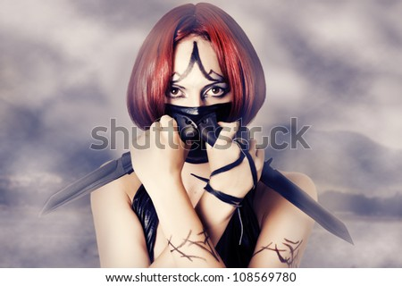 Fantasy style - red haired woman with dark creative make up, mask on her face and two combat knifes