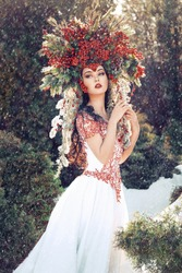 fantasy winter queen standing in falling snow, a beautiful woman in the crown of red berries and fur branches