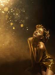 fantasy woman autumn queen, face in gold paint golden shiny skin. Fashion model girl princess posing. Black studio. Glamorous goddess. Crown, wreath roses flowers jewellery accessories metallic makeup