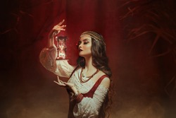 Fantasy woman creates magic. Gypsy girl witch holding magical hourglass in hands. Photo levitation.