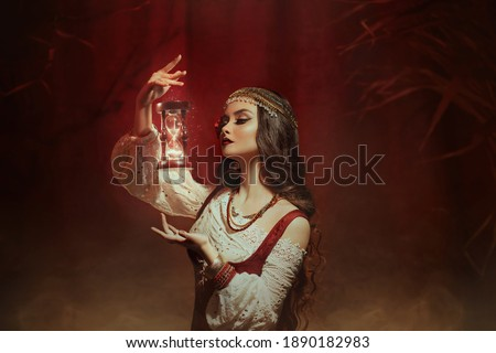 Fantasy woman creates magic. Gypsy girl witch holding magical hourglass in hands. Photo levitation. Foto d'archivio ©