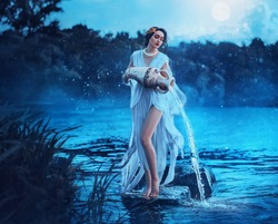 Fantasy woman Greek goddess zodiac sign Aquarius holds vintage earthenware jug in her hands and pours water into river. Background lake blue water, magic night, moon light stars. Astrology concept