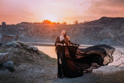 Fantasy woman in black fluttering fying chic silk dress. Dark gothic fashion glamorous character queen enjoying fabulous scenery autumn nature. Sunset warm red sun rays sunshine. Cliffs sky river.