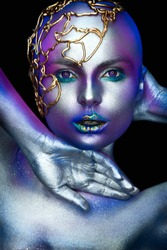 Fantasy woman portrait in blue colors. Young girl with body art on face and body.