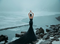 fantasy woman. young adult girl Snow Queen walks on frozen frost lake, river. Winter nature, ice cold covered water. Lady turned away, back train. Black dress mermaid Silhoette. Fashion model posing