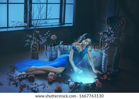 Fantasy young beautiful sorceress woman. long blue dress touch divine old mirror. Predictor future fairy tale Snow White. magic power wind light spell. Mystic gothic art photo dark black medieval room