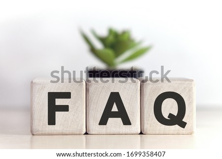 FAQ concept on wooden cubes and flower in a pot in the background