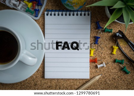 FAQ inscription written on book with globe,eyeglasses, calculator, camera, pencil and vase on wooden background with selective focus and crop fragment. Business and education concept Stock fotó ©