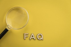 FAQ wood letters searching for facts truth news answers concept copy space flat lay on muted yellow