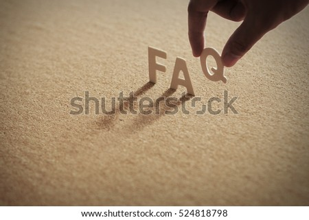 FAQ word on compressed board with human's finger at Q letter