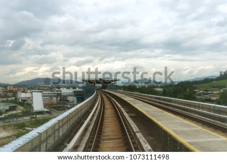 faraway view of the train platform against cloudy sky #1073111498