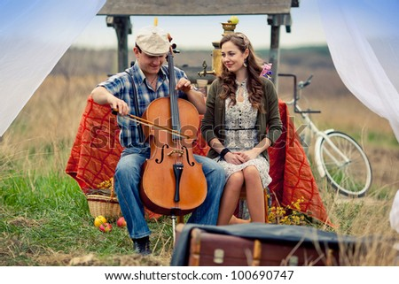 farm boy playing a girl on the cello in the field