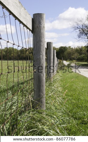 Farm fence by dirt road in American Midwest (shallow depth of field; focus on post in foreground)