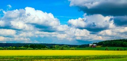 Farm field under cloudy sky. Farm land landscape. Farm field view