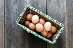 Farm Fresh Brown Chicken Hen Eggs in a Basket on Rustic Wood Counter Background with Copyspace, Horizontal