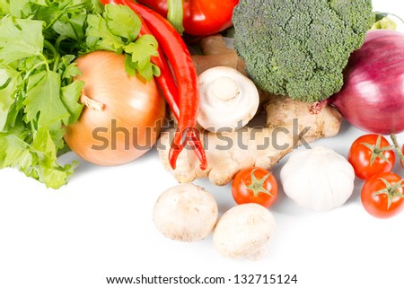 Farm fresh organic vegetables with an assortment of broccoli, mushrooms, chilli peppers, onions, parsley, ginger and tomatos on a white background