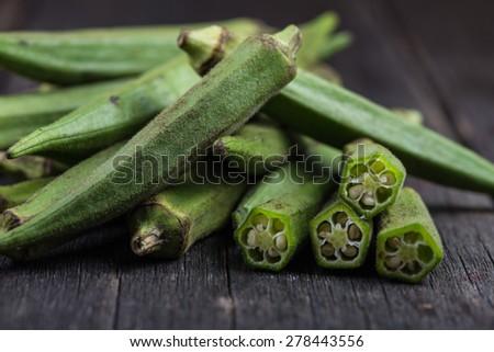 Farm fresh raw okra on wooden rustic table