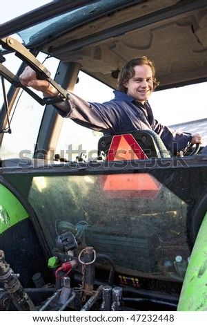 Farm hand looking out the rear window of a tractor, holding the lever - stock photo